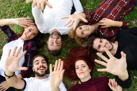 Plusieurs étudiants couchés sur l'herbe tendent leur main vers le ciel